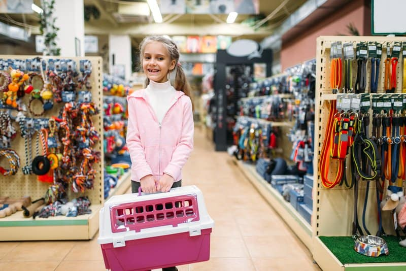 Happy little girl with carrier for cat in pet shop